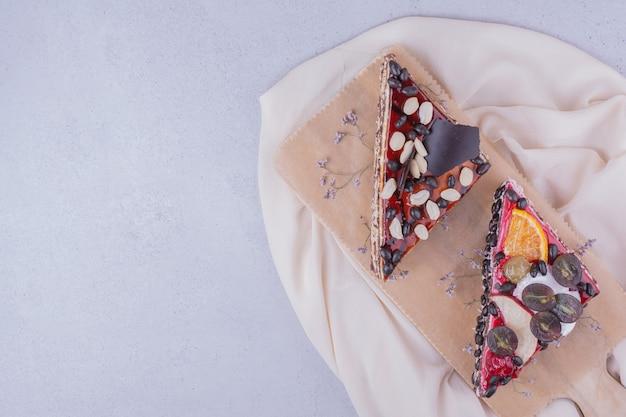 Trójkątne plastry ciasta czekoladowego z orzechami i owocami na drewnianym talerzu