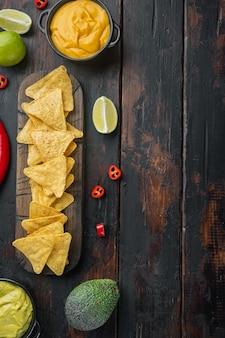 Trójkątny chips z żółtej kukurydzy z sosami, na starym drewnianym stole, widok z góry lub leżak na płasko