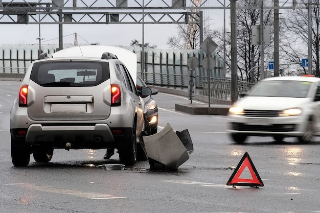 Trójkątny czerwony odblaskowy znak wypadku na drodze. zderzenie dwóch samochodów. zepsuty zderzak i maska. wypadek samochodowy na ulicy.