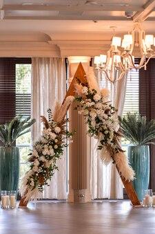 Trójkątny drewniany łuk z kompozycją trawy pampasańskiej, dalii i róż. dzień ślubu