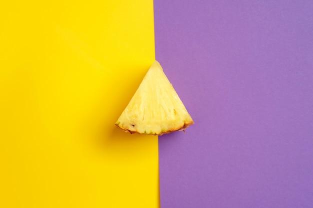 Trójkątny plasterek ananasa leży na żółto-fioletowym tle