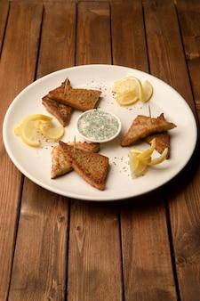 Trójkątny smażony chleb z sosem z koperkiem i cytryną