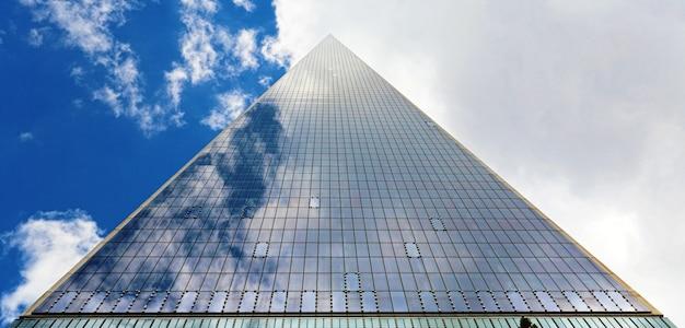Trójkątny wieżowiec i zachmurzone niebo
