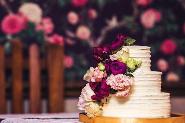 Trójpoziomowy tort weselny ozdobiony pięknymi kwiatami.