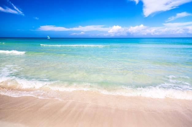 Tropikalna cudowna plaża varadero na kubie z żaglówką w słoneczny dzień z turkusową wodą i niebieskim niebem
