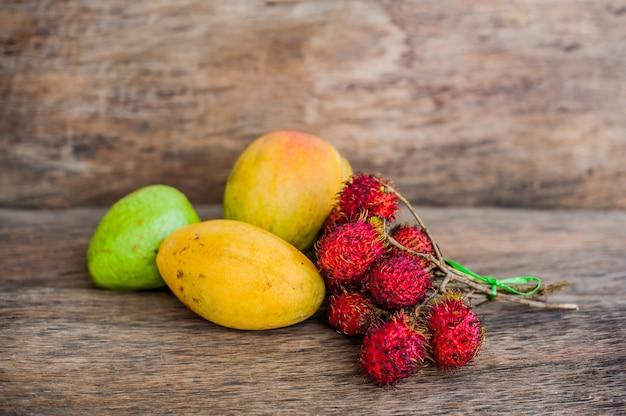 Tropikalna owoc na starym drewnianym tle. rambutan, banan, mango, guawa.