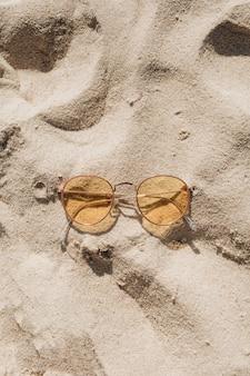Tropikalna piękna plaża z białym piaskiem, schodami i żółtymi słonecznymi okularami przeciwsłonecznymi