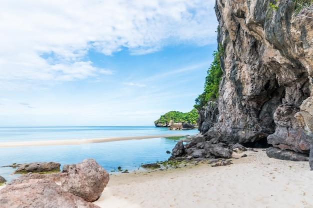 Tropikalna plaża i biały piasek latem, skały i błękitne niebo