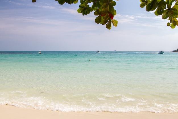 Tropikalna plaża z białym piaskiem i pięknym niebieskim tle nieba latem