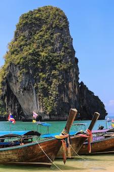 Tropikalna plaża z tradycyjnymi długimi ogon łodziami na kho poda, khabi, tajlandia
