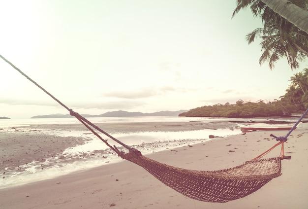 Tropikalna rajska plaża z palmami i tradycyjnym plecionym hamakiem