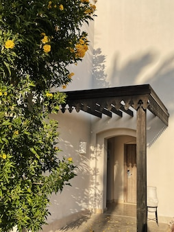 Tropikalna roślina z żółtymi kwiatami na beżowej ścianie budynku domu