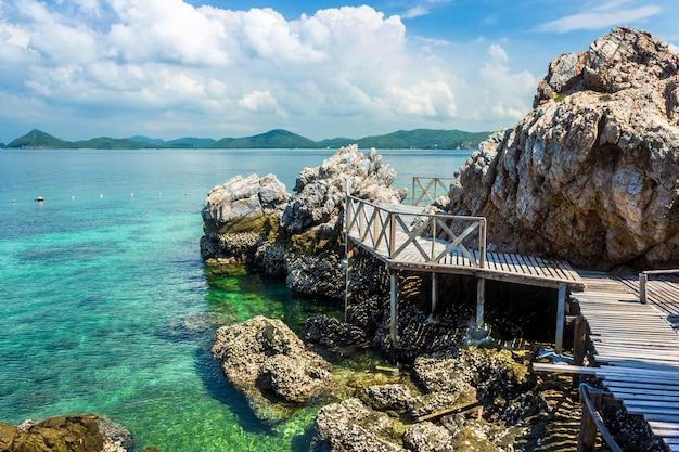 Tropikalna wyspy skała i drewno most na plaży z niebieskim niebem.