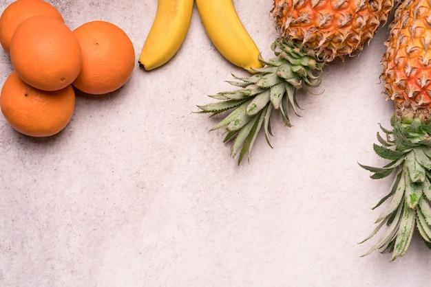 Tropikalne i sezonowe letnie owoce. ananasowe pomarańcze i banany ułożone, zdrowe życie