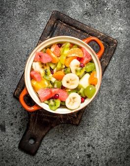 Tropikalne jedzenie. sałatka owocowa w misce. na tle rustykalnym.