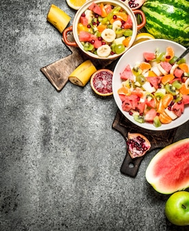 Tropikalne jedzenie. sałatka ze świeżych owoców tropikalnych w miskach. na tle rustykalnym.