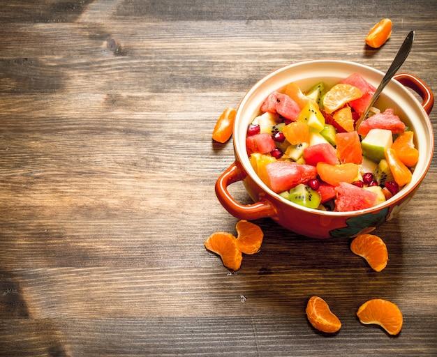 Tropikalne jedzenie. świeża sałatka z owoców egzotycznych. na drewnianym stole.