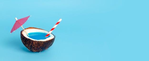 Tropikalne lato i wakacje minimalna koncepcja. kokos na niebieskim tle z koktajl słomy. wakacje, podróże, pomysł na plażę.