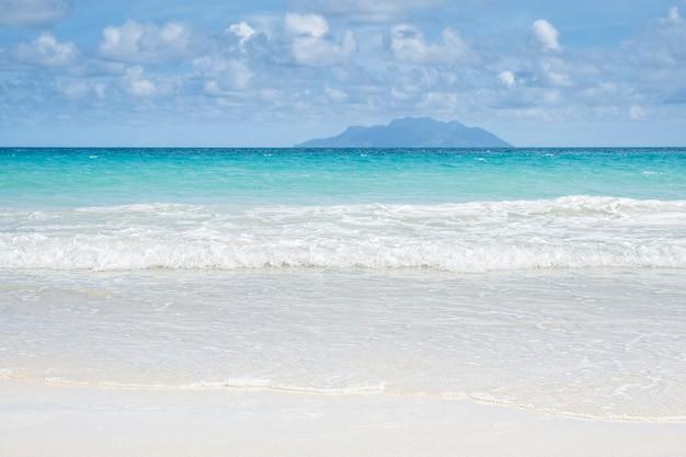 Tropikalne lato morze z gładkimi falami błękitne niebo piasek i samotna odległa wyspa, koncepcja tropikalnych wakacji, miejsce kopiowania