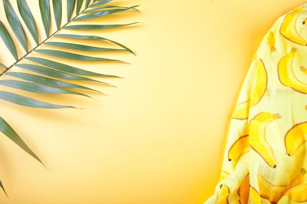 Tropikalne liście i ręcznik plażowy na żółtej ścianie.