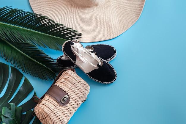 Tropikalne liście na niebieskim tle z letnimi akcesoriami. pojęcie wakacji letnich.