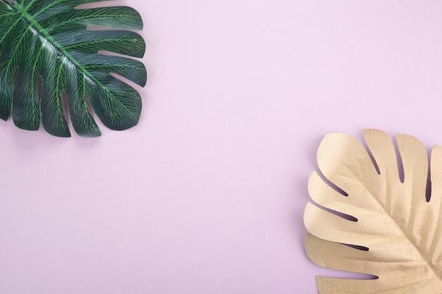 Tropikalne liście złote, zielone na różowym tle. tropikalna palma. streszczenie tło nowoczesne. tapeta na plaży.