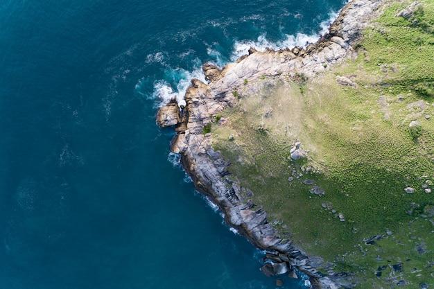 Tropikalne morze z falą rozbijającą się na brzegu morza i wysokiej górze