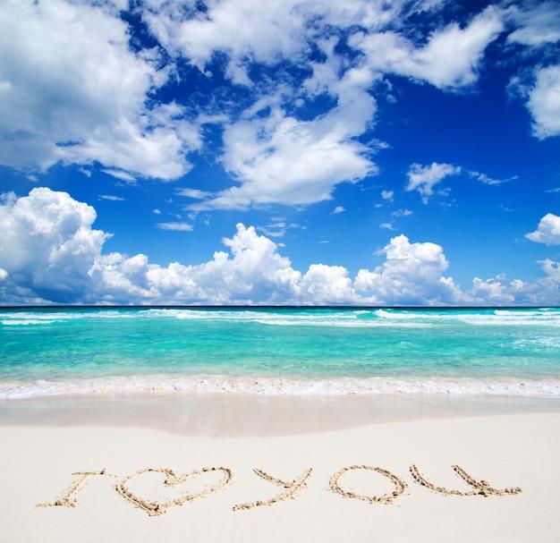 """Tropikalne morze z tekstem """"kocham cię"""" napisanym w piasku"""