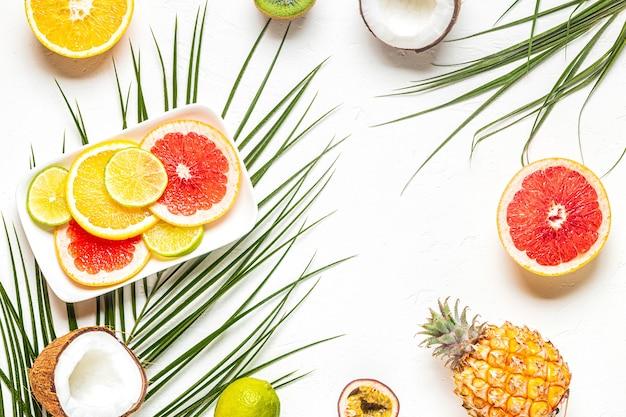 Tropikalne owoc i palma liście na białym tle