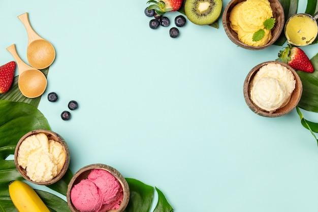 Tropikalne owoce i rośliny z różnych lodów w łupinach orzecha kokosowego na niebieskim tle