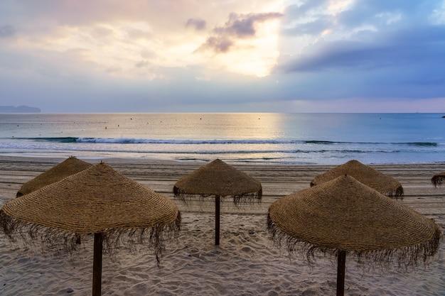 Tropikalne parasole na piaszczystej plaży o zachodzie słońca przy spokojnym morzu.