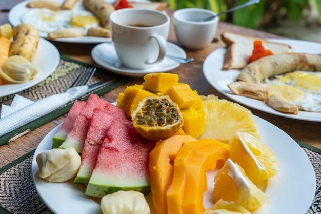 Tropikalne śniadanie z owocami, kawą i jajecznicą i bananowym naleśnikiem dla dwojga na plaży w pobliżu morza w hotelowej restauracji, wyspa zanzibar, tanzania, afryka, z bliska
