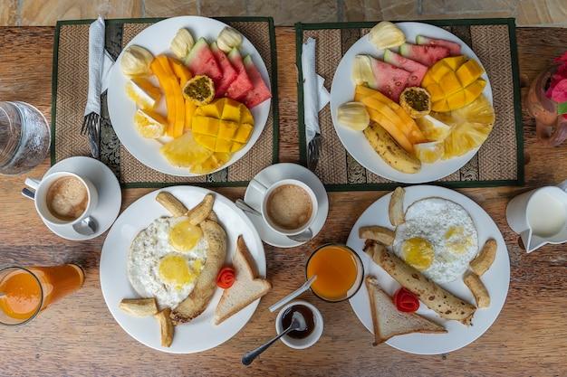 Tropikalne śniadanie z owocami, kawą i jajecznicą i naleśnikiem bananowym dla dwojga na plaży w pobliżu morza w hotelowej restauracji, wyspa zanzibar, tanzania, afryka, z bliska. widok z góry, nakrycie stołu.