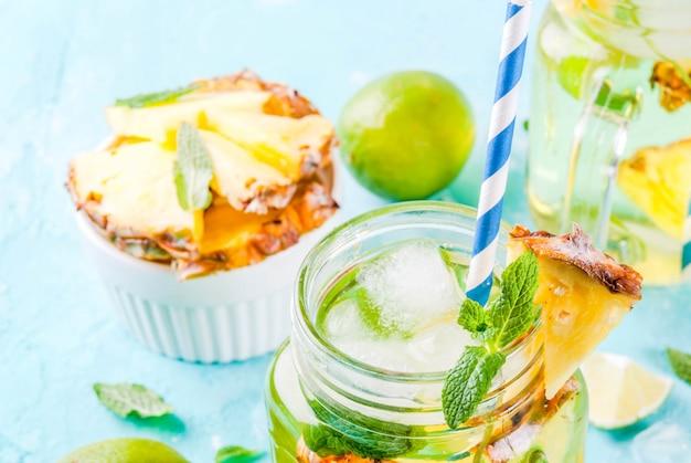 Tropikalny napój ananasowy mojito lub lemoniada ze świeżą limonką i miętą jasnoniebieskie tło