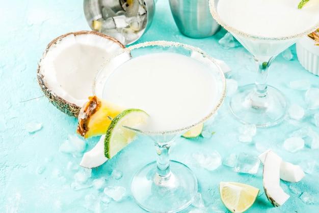 Tropikalny napój mrożony kokosowy ananasowy margaritas z mrożonym sokiem z ananasów tequili pina colada i limonką jasnoniebieskie tło