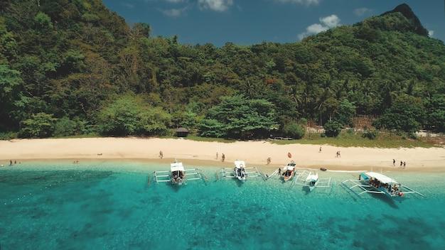 Tropikalny rejs z odpoczywającymi ludźmi na antenie brzegu oceanu