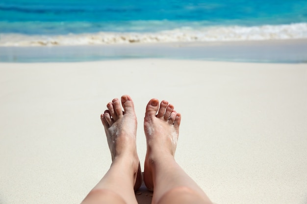 Tropikalny tło. stopa na plaży w pobliżu morza. koncepcja rekreacji