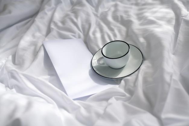 Troska, dobre samopoczucie. złożona kartka papieru z notatką, filiżanką i spodkiem na zmiętej czystej białej pościeli w miękkim świetle dziennym