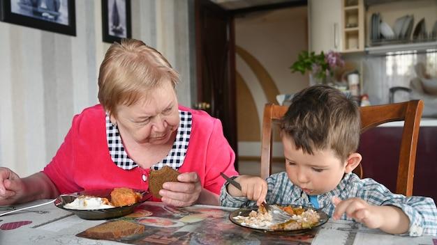 Troskliwa babcia z wnukiem jedzą.