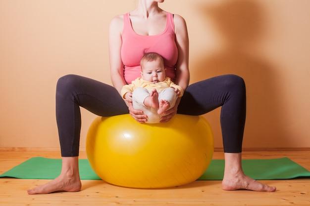 Troskliwa mama ćwicząca sport z dzieckiem na fitball