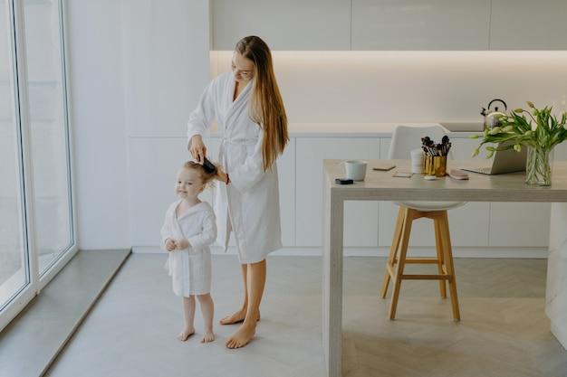 Troskliwa mama czesze włosy swojej małej córeczki
