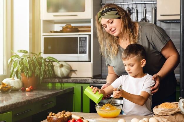 Troskliwa mama pomaga małemu przedszkolakowi przygotować ciasteczka, uśmiechnięta kochająca mama uczy się gotowania z małym chłopcem, robiąc razem obiad w weekend w kuchni