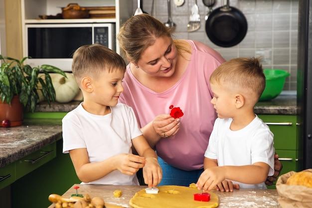 Troskliwa mama pomaga małym synom w wieku przedszkolnym przygotować ciasteczka, uśmiechnięta kochająca mama uczy się gotowania z małym dzieckiem, robiąc razem obiad w weekend w kuchni