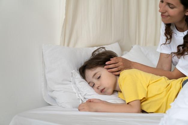 Troskliwa matka pieszcząca głowę dziecka, syna śpiącego w łóżku rano, czule budzi dziecko w wieku przedszkolnym