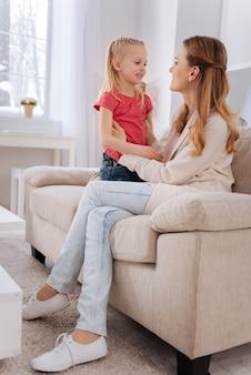 Troskliwa matka. przyjemna miła zachwycona kobieta uśmiechnięta i patrząc na córkę siedząc na sofie