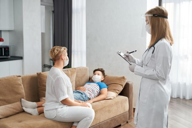 Troskliwa matka siedzi obok syna, podczas gdy lekarz robi badanie