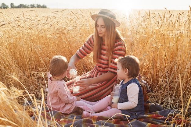 Troskliwa pomocna matka siedząca na kocu przy polu pszenicy z małymi córkami, napełniająca szklanki mlekiem z butelki, ubrana w sukienkę i kapelusz, dziecko zachowujące się we właściwy sposób. koncepcja macierzyństwa.