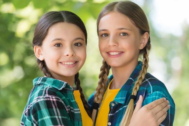 Troskliwe środowisko. szczęśliwe dziewczyny w warkoczach uśmiechają się. produkty do pielęgnacji skóry. wakacje letnie. kosmetyki do pielęgnacji włosów. salon piękności. opieka nad dziećmi i pediatryczna opieka zdrowotna. opieka społeczna.