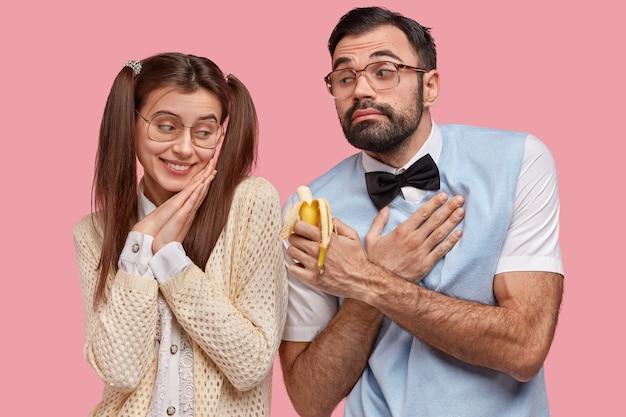 Troskliwy chłopak z grubym zarostem, elegancko ubrany, wygląda niezgrabnie, trzyma rękę na piersi, sugeruje dziewczynie ugryzienie banana