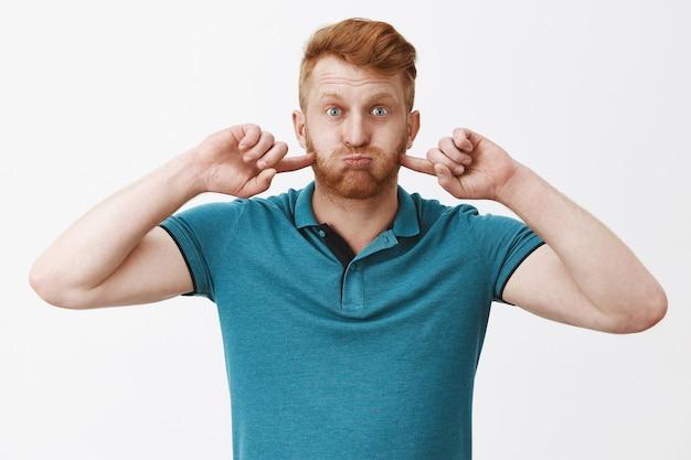 Troskliwy figlarny i uroczy rudowłosy mężczyzna w zielonym modnym polo, nadąsany i szturchający policzki palcami wskazującymi, wydychając powietrze, wstrzymując oddech w ustach nad szarą ścianą